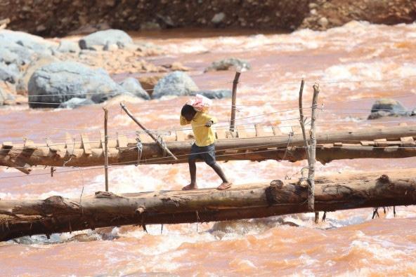 サイクロン「イダイ」によって家々が流されたルシツ渓谷の地域で、水面が迫った橋をわたる男の子。