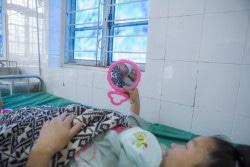 ベトナムの病院で、低体重で生まれた娘を抱く母親。