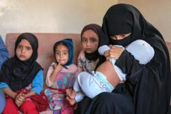 サヌアの自宅で、不安げな表情で座る子どもたち。