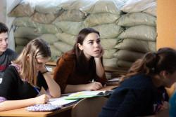 窓辺に土嚢が積まれた教室で勉強する13歳のマリアさん。