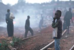 口を押さえて線路の側に立つケニアの男の子。