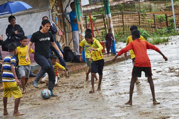 雨季入りしたばかりのバングラデシュ。2日間にわたるキャンプ訪問も、時折強い雨にうたれながらとなった。「室内でのリフティングなどにしては?」との現地スタッフの問いに、長谷部大使は「大丈夫ですよ!」と長靴のまま、泥だらけになりながら、子どもたちとサッカーで交流。