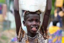 ユニセフが支援する給水所で安全な水を汲み、家に運ぶ10歳の女の子(南スーダン)