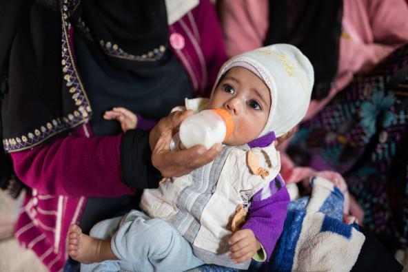 祖母からミルクを与えられるアリちゃん。母親を亡くしたアリちゃんは、伯母と祖母によって育てられている。
