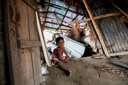 A boy sits in his destroyed home, after Cyclone Fani hit Bangladesh at Dokhin Koralia in Vola, Bangladesh on May 07, 2019. A severe cyclonic storm, Fani, struck Bangladesh in the early hours of 4 May 2019, bringing with it high winds and heavy rainfall.  Almost 1.3 million people had been evacuated to cyclone shelters across the affected areas of western and southern Bangladesh.  UNICEF had pre-positioned emergency lifesaving supplies to meet the needs of up to 100,000 people in the western areas of the country and Cox's Bazar, as well as contingency agreements with partners which are ready to be activated to provide emergency WASH, nutrition, health, child protection and education services.