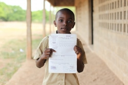 Hermann Namouh, 9, holds his birth certificate, outside Banque Africaine de Développement (African Development Bank) Zanzan II Primary School, in the town of Bondoukou, Bondoukou Department, Zanzan Region.  In November 2011, Côte d'Ivoire continues to recover from the violence that erupted after the 28 November 2010 presidential election. Over 185,000 people are still displaced, while more than 163,000 Ivoirians remain refugees in nearby countries, mainly Liberia. In the north-eastern Zanzan Region, the conflict worsened an already precarious existence where poverty affects over half of the population and food insecurity remains prevalent. Over 40 per cent of children are chronically malnourished, while the region's rate of moderate acute malnutrition – 7.7 per cent – is the highest in the country. Over 30 per cent of the population lacks access to safe drinking water, while nearly 70 per cent lacks access to improved sanitation facilities. The region has a 16 per cent under-five morality rate, exceeding the already high national figure. Regional primary school enrolment is a low 40 per cent and is even lower among girls. Further, approximately 60 per cent of the region's children do not possess a birth certificate, a basic requirement for accessing social services. In the context of a refocused equity approach, UNICEF, in coordination with the Government and other partners, continues to support efforts in health, including the treatment and prevention of HIV, nutrition, water, sanitation and hygiene, education and child protection.