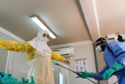 A health worker is doffing the personal protection suit he has been wearing. There are specific protocols for donning and doffing in the context of Ebola to ensure the health worker is not infected.  For every layer of clothes, a sprayer is disinfecting the health worker with a chlorine solution. UNICEF is training frontline health workers on correct infection prevention and control (IPC) as part of the preparedness activities in South Sudan. WHO has rated the risk of the disease spreading from DRC to South Sudan as very high.