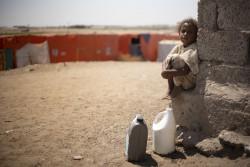 容器に水を汲んで運ぶ国内避難民キャンプに滞在する子ども。(2019年2月撮影)