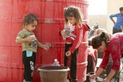 ユニセフとパートナーから給水された水をボトルに汲む女の子たち。(2019年10月16日撮影)